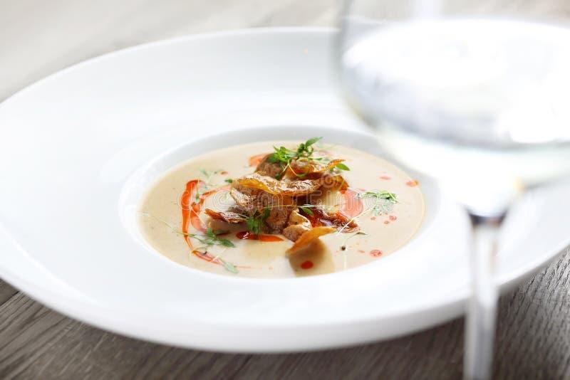De soep van de selderieroom met aardappelen in de schil en een glas witte wijn stock afbeeldingen