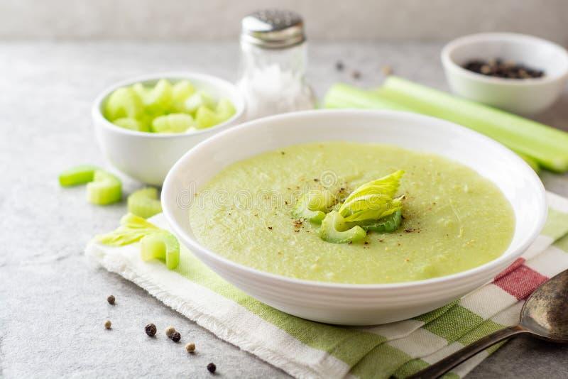 De soep van de selderieroom in witte plaat op grijze steenachtergrond stock afbeeldingen