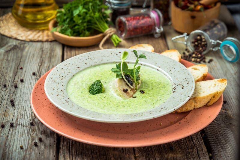 De soep van de spinazieroom in kom op witte rustieke lijst, hoogste mening royalty-vrije stock afbeeldingen