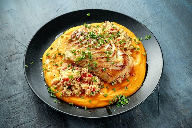 De soja-verglaasde filet van het kabeljauwlendestuk met kouskoussalade op de puree van de butternutpompoen stock foto's