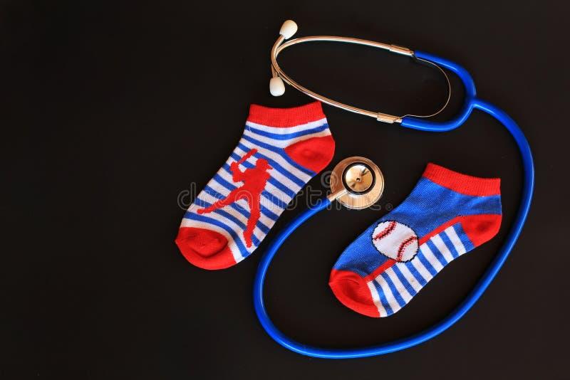De sokken en de stethoscoop van de kinderenjongen, die kinderengezondheidszorg/pediatrische zorg symboliseren stock foto's