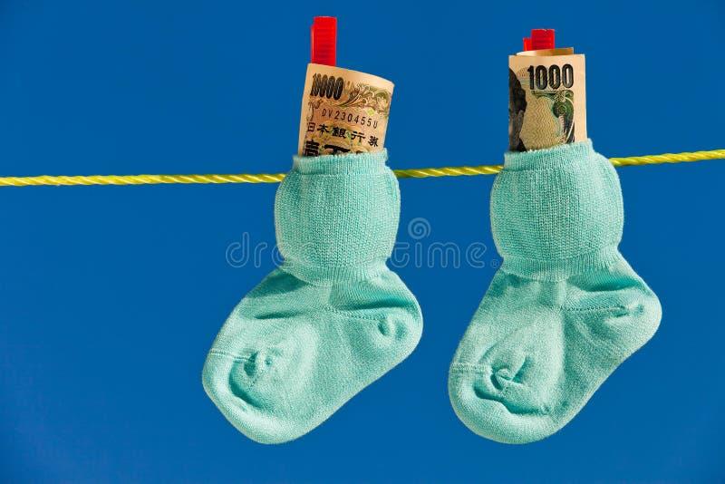 De sokken van de baby op drooglijn met Yenbankbiljetten royalty-vrije stock afbeeldingen
