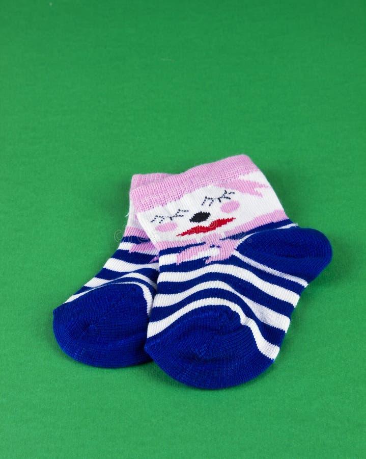 De sokken van de baby op geïsoleerdeo groen stock foto's