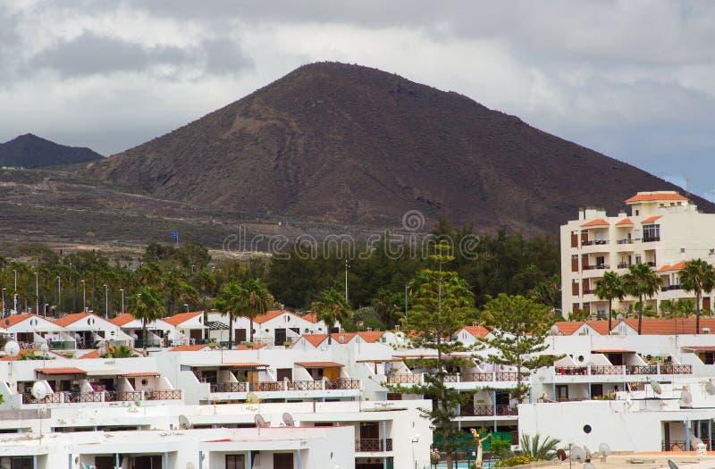 De sombere vulkanische bergen en de heuvels die Playa Las Amerika en Los Christianos in Tenerife in de Canarische Eilanden op a o stock afbeelding