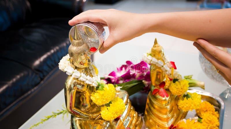 De Songkrandag, Thais cultuurconcept, Handvrouw gebruikt de strookslag aan het gouden standbeeld van Boedha stock fotografie
