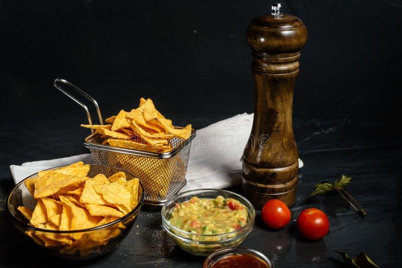 De spaanders van de Nachostortilla met gesmolten die kaas met guacamole wordt gediend royalty-vrije stock afbeeldingen