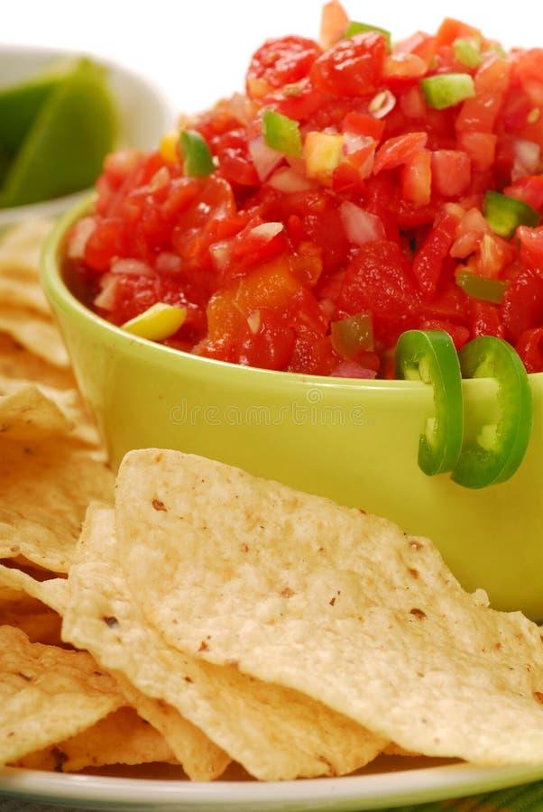 De spaanders van de tortilla met salsa en kalk stock foto