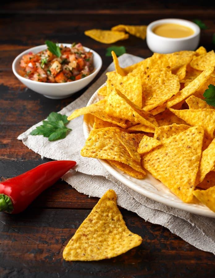 De spaanders van tortillanachos met kaassaus, guacamole en de onderdompeling van tomatensalsa Kalk Spaanse peperspeper stock afbeelding