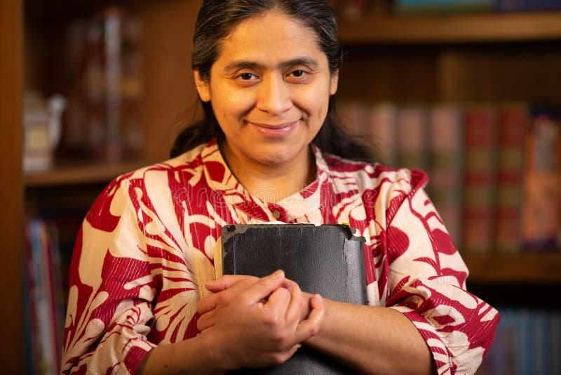 De Spaanse Bijbel van de Vrouwenholding en het Bekijken direct de Camera royalty-vrije stock foto