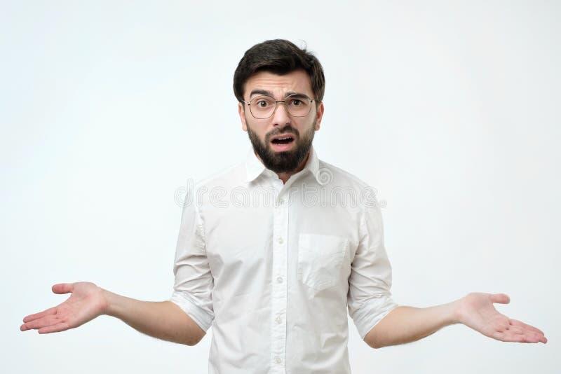 De Spaanse mens in wit overhemd werpt op van hem indient ongeloof royalty-vrije stock afbeelding