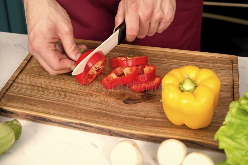 De Spaanse peper van de handplak met ceramisch mes royalty-vrije stock foto