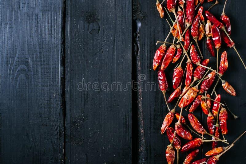 De Spaanse peperpeper op een zwarte houten uitstekende achtergrond, bespot en plaatst omhoog achtergrond, droge Spaanse peperspep royalty-vrije stock afbeelding
