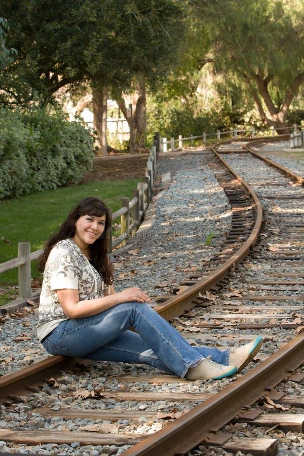De Spaanse vrouw zit op treinsporen stock foto