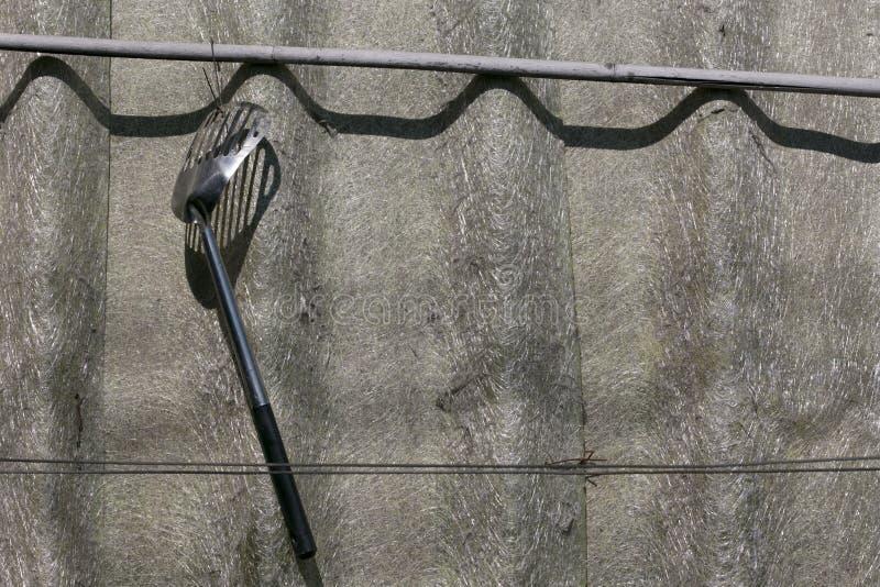 De spade van pan hangt op dak stock fotografie