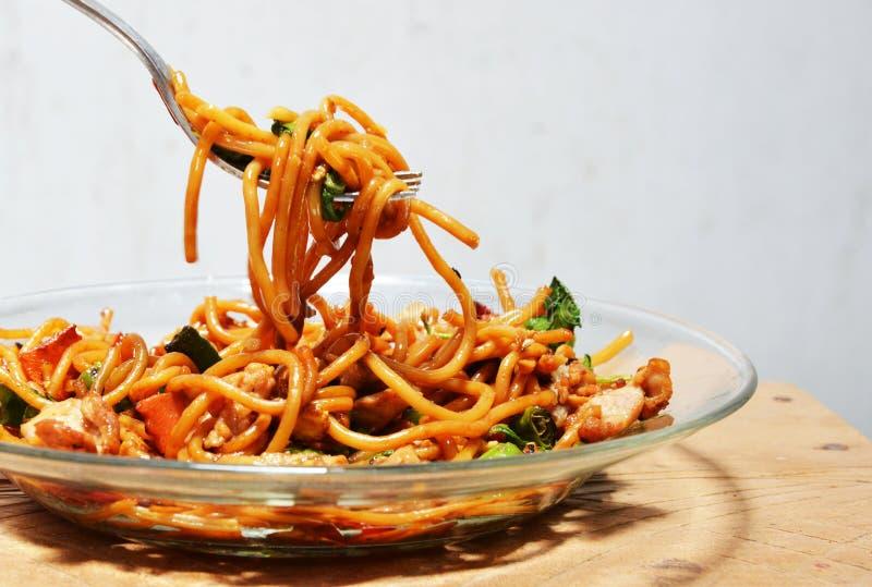 De spaghetti beweegt gebraden met kruidig varkensvlees op vork stock foto