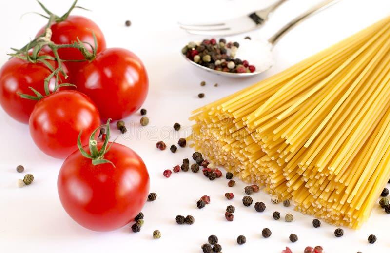 De spaghetti ligt op een witte achtergrond, samen met kersentomaten, een lepel en een vork royalty-vrije stock afbeeldingen