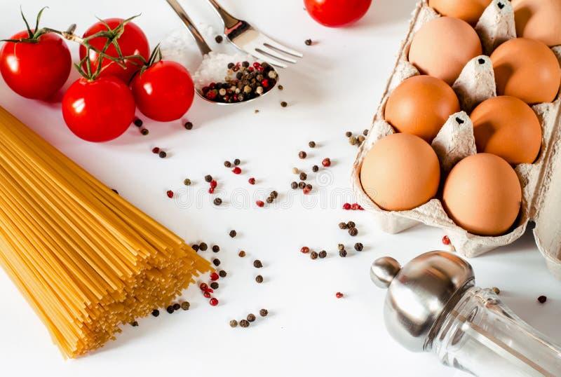 De spaghetti ligt op een witte achtergrond, samen met kersentomaten, een lepel en een vork stock foto
