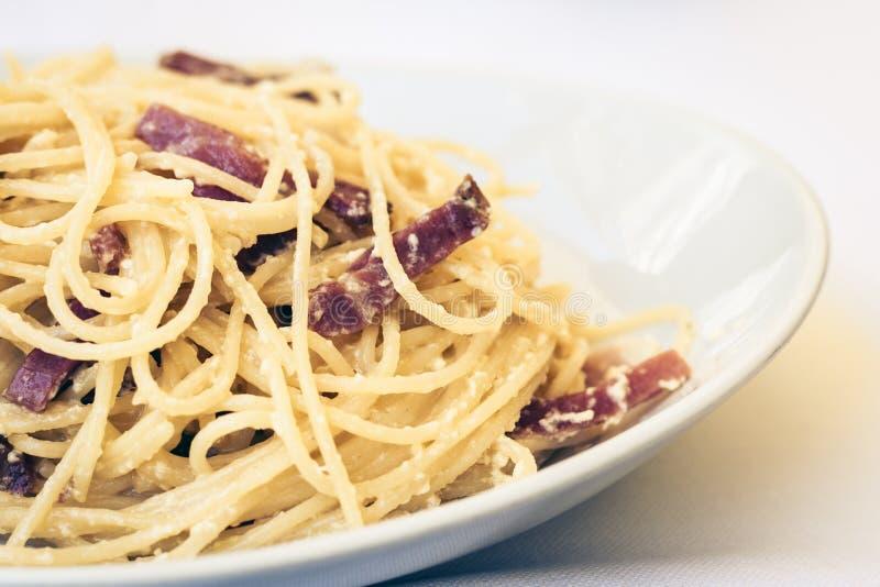 De spaghetti van deegwarencarbonara met ham, bacon en verse parmezaanse kaas op de witte plaat in restaurant in Catanië, Sicilië, stock afbeelding