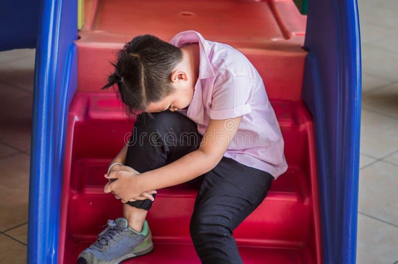 De spanning en de eenzaamheid van Aziatische jongens in de schoolspeelplaats stock afbeelding