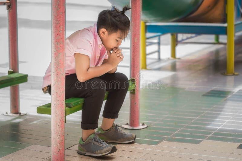 De spanning en de eenzaamheid van Aziatische jongens in de schoolspeelplaats stock afbeeldingen