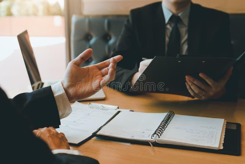De spanning in de gespreksruimte tussen de manager en het personeel die over de werknemer spreken werkt geschiedenis stock foto