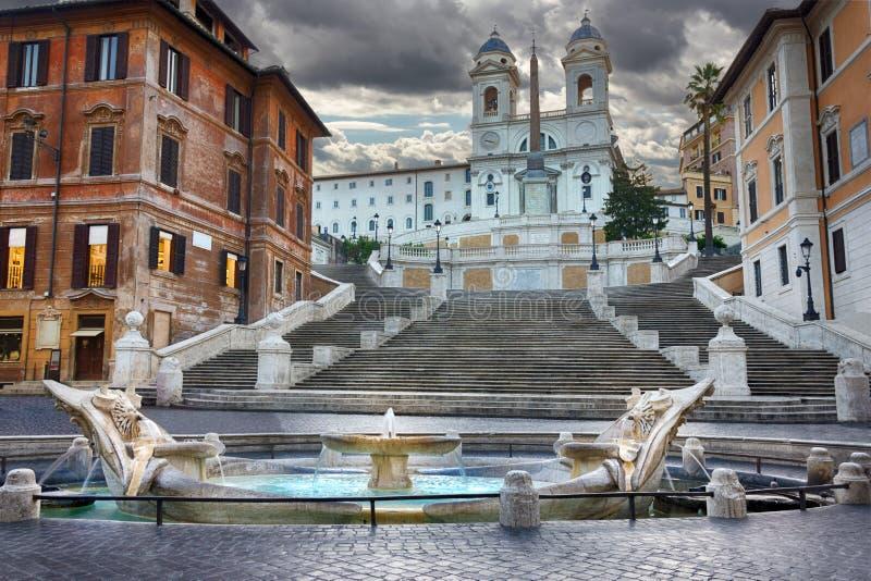 De spanska momenten, den Trinita deien Monti och `-springbrunnen av barkass`en i Piazza di Spagna för åskvädret arkivbilder