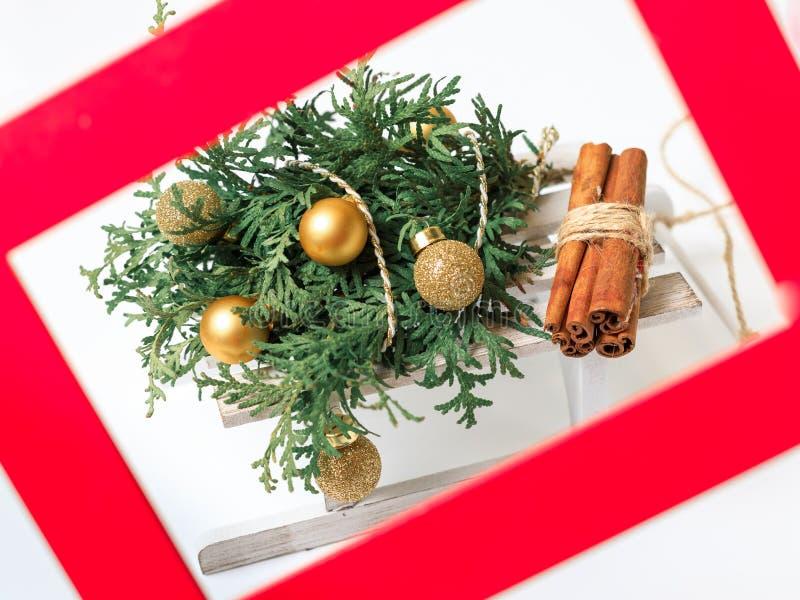De spar van het nieuwjaar de verfraaide Kerstmis gouden gebieden en een bundel van brandhout Een rood kader voor een foto royalty-vrije stock foto