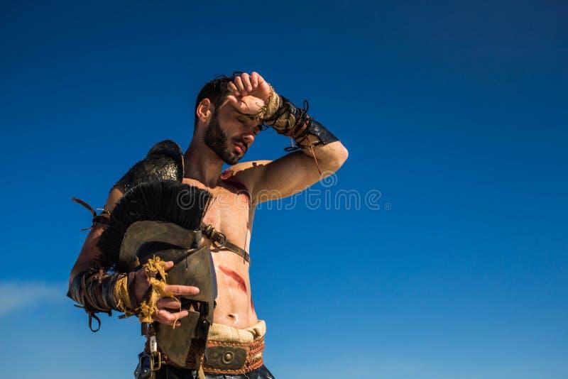 De Spartaanse strijder veegt het zweet van zijn voorhoofd af royalty-vrije stock afbeelding