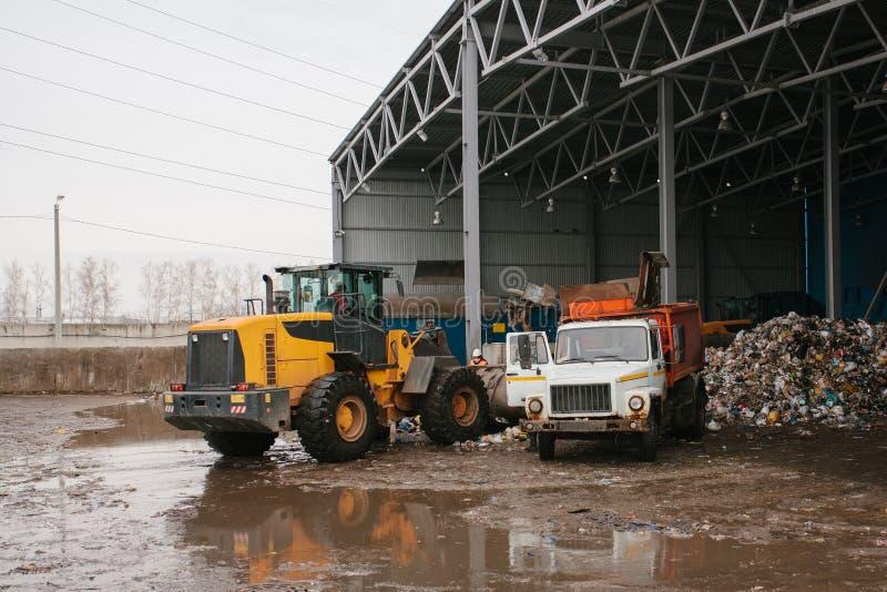 De speciale machines of de bulldozer werken aan de plaats van afval het leegmaken bij de installatie voor afvalverwijdering royalty-vrije stock afbeelding
