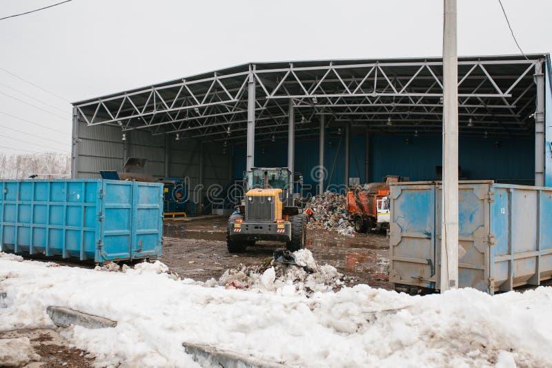 De speciale machines of de bulldozer werken aan de plaats van afval het leegmaken bij de installatie voor afvalverwijdering stock fotografie