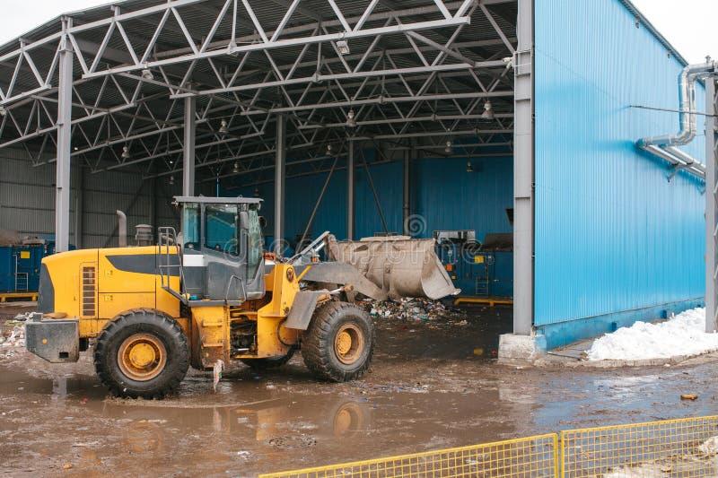 De speciale machines of de bulldozer werken aan de plaats van afval het leegmaken bij de installatie voor afvalverwijdering stock foto's