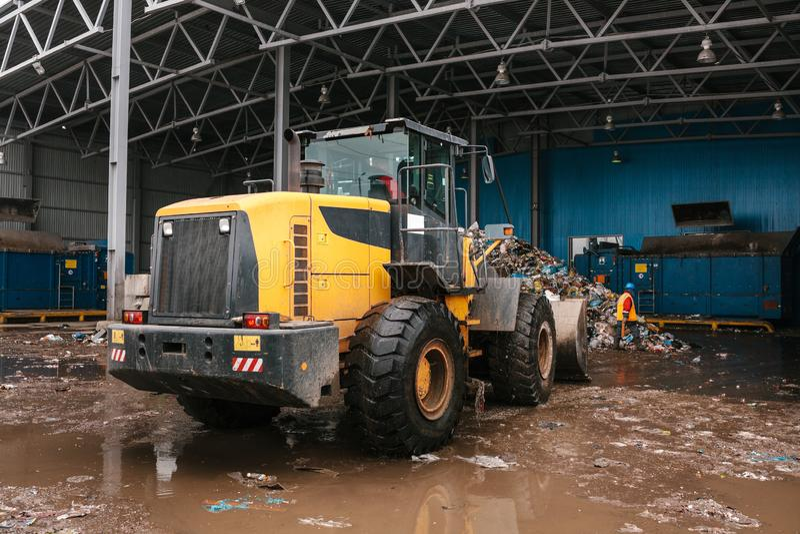 De speciale machines of de bulldozer werken aan de plaats van afval het leegmaken bij de installatie voor afvalverwijdering royalty-vrije stock foto