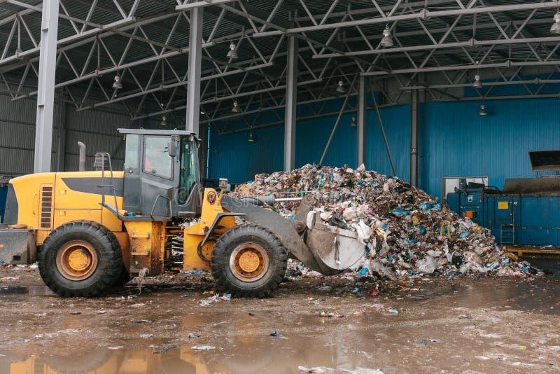 De speciale machines of de bulldozer werken aan de plaats van afval het leegmaken bij de installatie voor afvalverwijdering royalty-vrije stock fotografie