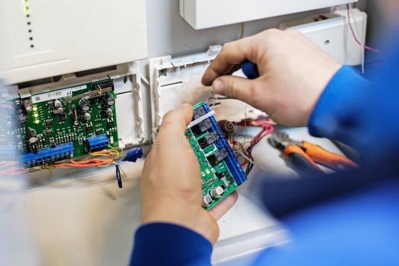 De specialistenhanden verbinden de draad met de Raad met spaanders Reparatie, behoud en aanpassing van instrumentatie en materiaa stock foto's