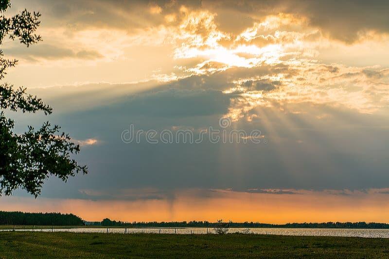 De spectaculaire zonsondergang over meer Guelpe Gülper ziet met zonnestralen die door dikke wolken glanzen stock afbeeldingen