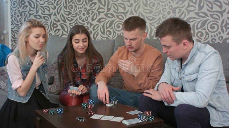 De speelkaarten van tienervrienden thuis royalty-vrije stock afbeeldingen