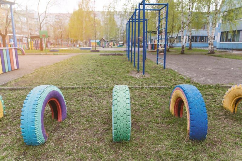 De Speelplaats van kinderen in de kleuterschool Multi-colored wielspelen De oude wielen van auto's zijn geschilderd in verschille royalty-vrije stock afbeelding