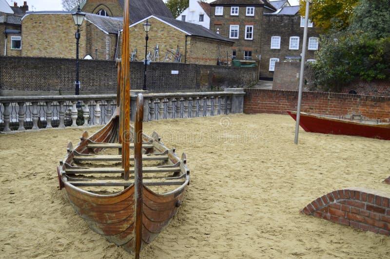 De Speelplaats van kinderen met een Houten Boot op Zand in Twickenham Londen het UK royalty-vrije stock fotografie