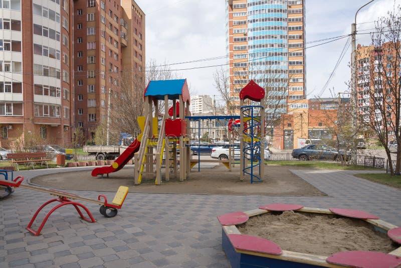 De speelplaats van kinderen met een zandbak en schommeling in de binnenplaats van de huizen in de stad van Krasnoyarsk royalty-vrije stock foto