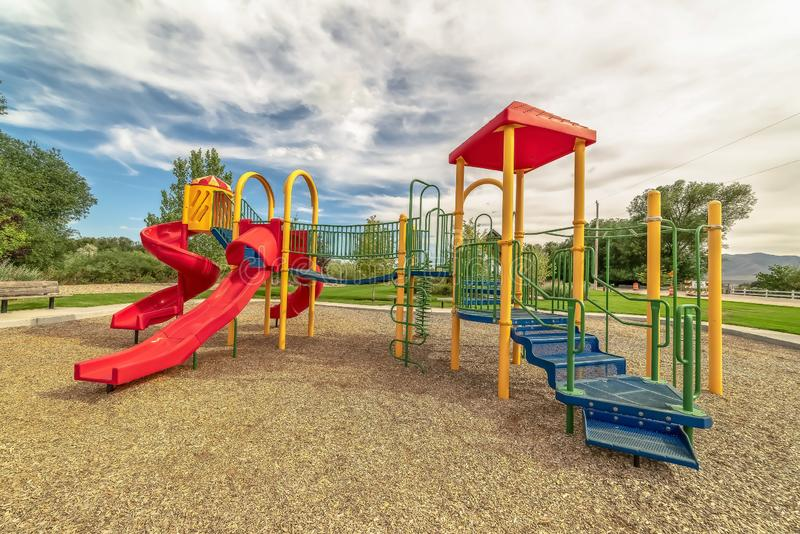 De speelplaats van kinderen op een het ontspannen park met mening van bomen en verre berg stock afbeeldingen