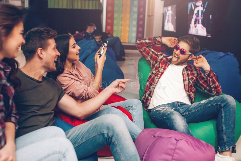De speelse grappige mensen zitten in het spelen ruimte en hebben pret Kerelslijtage zonnebril en het stellen Zijn vrienden die be stock foto