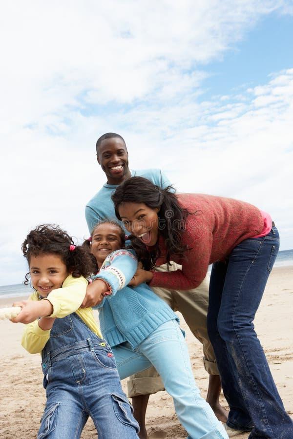 De speeltouwtrekwedstrijd van de familie op strand royalty-vrije stock foto