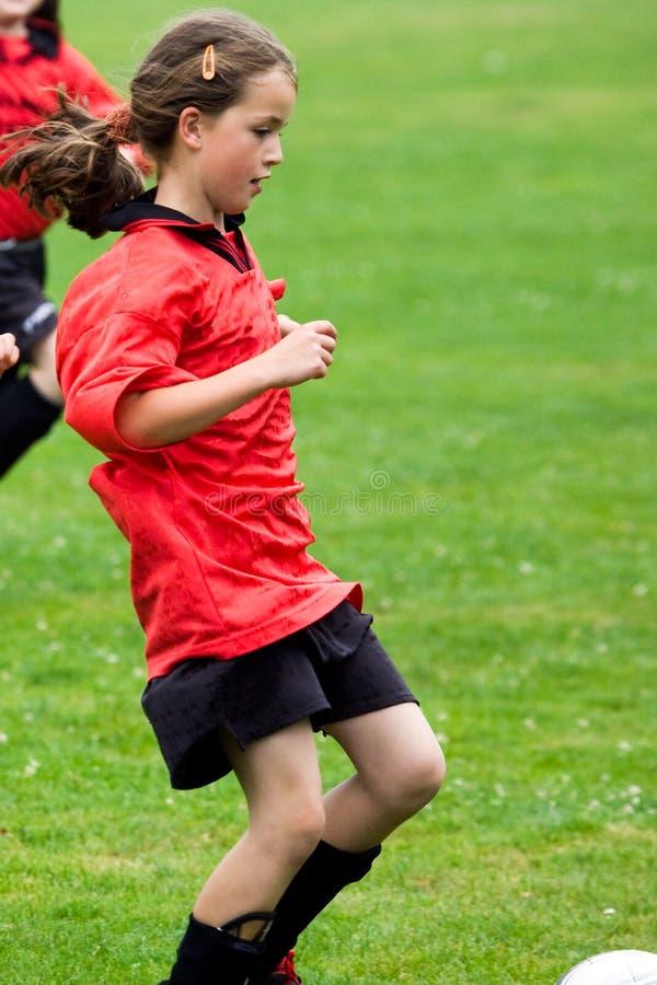 De speelvoetbal van het meisje stock afbeeldingen