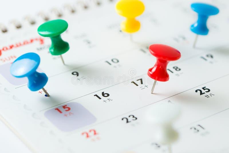 De speld van de duimkopspijker op kalender royalty-vrije stock afbeeldingen