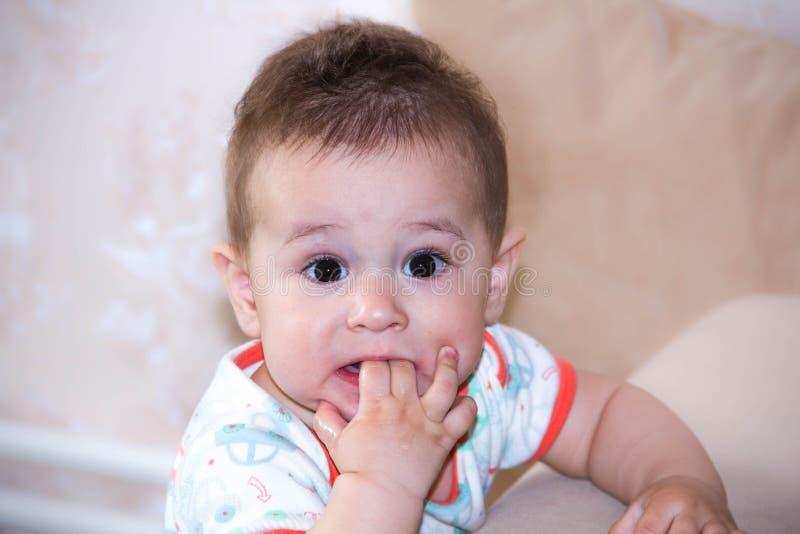 De spelen van de babyjongen met vingers in mond en gelukkige gelaatsuitdrukking Portret van het kruipende glimlachen Tandjes krij stock fotografie