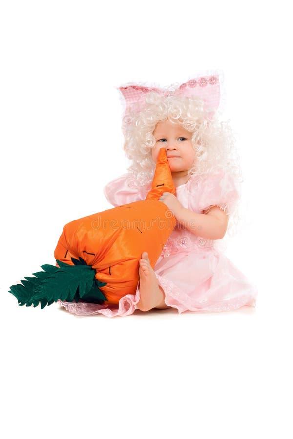 De spelen van het babymeisje met een wortel.  stock fotografie
