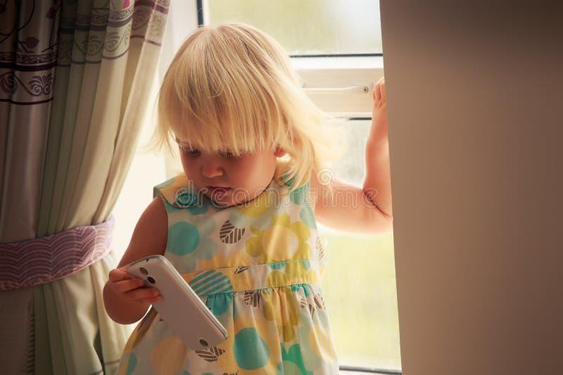de spelen van het blondemeisje met smartphone stock afbeelding