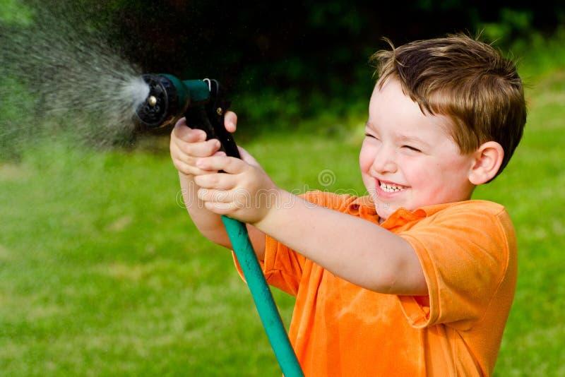 De spelen van het kind met waterslang in openlucht stock afbeelding