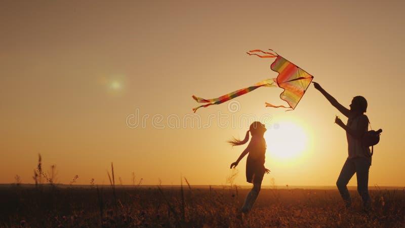 De spelen van het mamma met haar dochter Lanceer zorgeloos een vlieger Het gelukkige leven, het concept van de de zomeractiviteit royalty-vrije stock fotografie