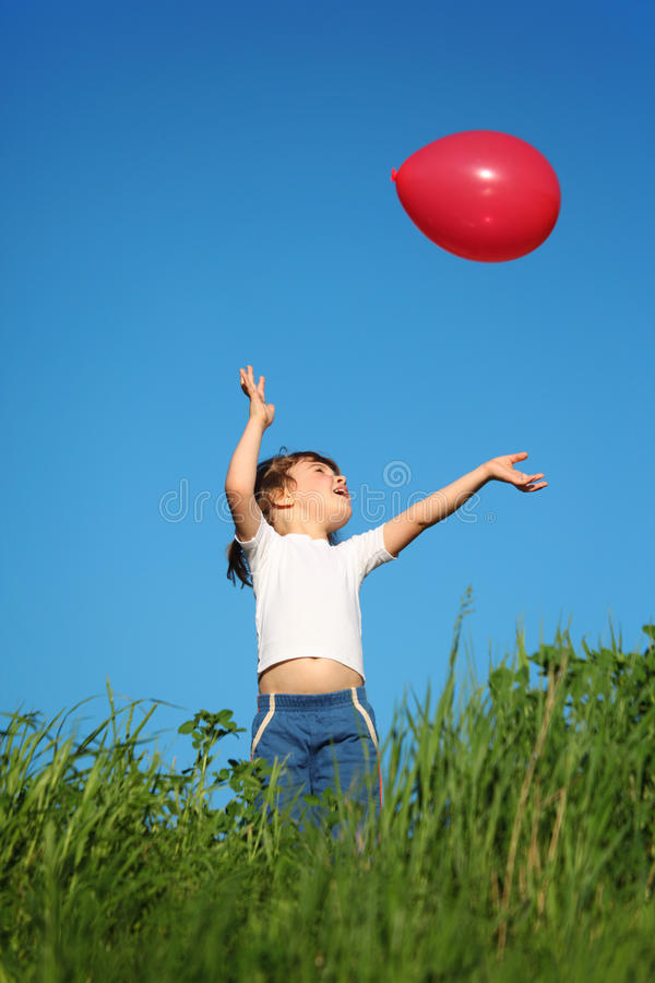 De spelen van het meisje met rode ballon in gras stock fotografie